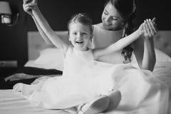 Moder och dotter som har gyckel på sängen Arkivbild