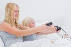 Moder och dotter som har gyckel som spelar videospel Royaltyfria Bilder