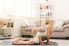 Moder och dotter som hemma gör yogaövningar arkivfoto