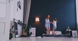 Moder och dotter som hoppar på sängen, lycka som är glad arkivfilmer