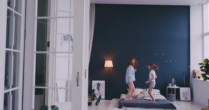Moder och dotter som hoppar p? s?ngen, lycka som ?r glad lager videofilmer