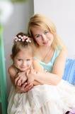Moder och dotter som inomhus omfamnar royaltyfria bilder