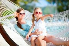 Moder och dotter som kopplar av i hängmatta Arkivfoton