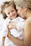 Moder och dotter som kopplar av i säng Fotografering för Bildbyråer