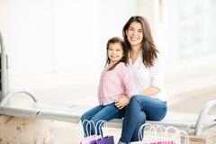 Moder och dotter som kopplar av på en bänk utanför galleria royaltyfria bilder
