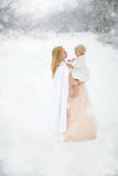 Moder och dotter som kramar lyckligt i snöstorm fotografering för bildbyråer