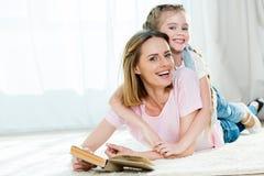 Moder och dotter som kramar, medan ligga på matta och läseboken Arkivfoto