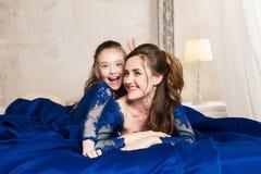 Moder och dotter som kramar och ser kameran lyckligt älska för familj Modern och dottern i härlig lång lyx slösar dres Arkivbilder