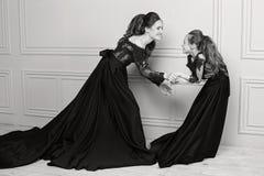 Moder och dotter som kramar och ser kameran lyckligt älska för familj Modern och dottern i härlig lång lyx slösar dres Royaltyfri Fotografi