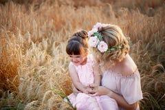 Moder och dotter som kramar på hennes huvud en girland av rosor, mjuk bild royaltyfri bild