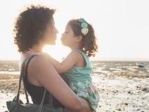 Moder och dotter som kysser på solnedgången på stranden Royaltyfri Fotografi