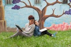 Moder och dotter som läser en bok arkivbilder