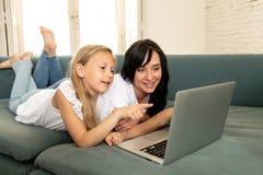 Moder och dotter som ler och har gyckel som spelar och surfar tillsammans på internet på en bärbar dator royaltyfri bild