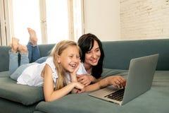 Moder och dotter som ler och har gyckel som spelar och surfar tillsammans på internet på en bärbar dator royaltyfria foton