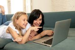 Moder och dotter som ler och har gyckel som spelar och surfar tillsammans på internet på en bärbar dator fotografering för bildbyråer
