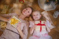 Moder och dotter som ligger med gåvor under julgranen arkivbild