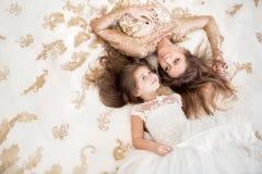 Moder och dotter som ligger på golvet i härliga vita dres Arkivbild