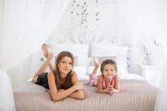 Moder och dotter som ligger på sängen Royaltyfri Foto