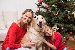 Moder och dotter som omfamnar hunden Arkivbild