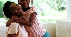 Moder och dotter som omfamnar sig i vardagsrum stock video
