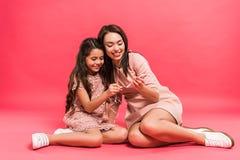 Moder och dotter som pluggar hörlurar Arkivbilder