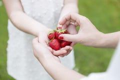 Moder och dotter som rymmer några jordgubbar Royaltyfri Fotografi