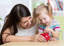Moder och dotter som sätter mynt in i den piggy gruppen fotografering för bildbyråer