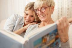 Moder och dotter som ser familjfotoalbumet royaltyfri fotografi