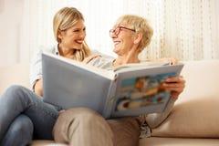 Moder och dotter som ser familjfotoalbumet royaltyfria bilder