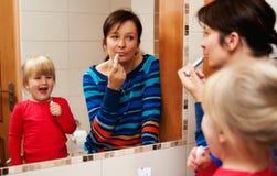 Moder och dotter som ser in i spegeln Arkivfoton