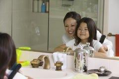 Moder och dotter som ser reflexion i badrumspegel Royaltyfria Foton