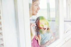 Moder och dotter som ser till och med fönstret Royaltyfria Foton