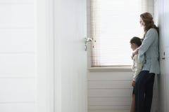 Moder och dotter som ser ut ur fönsterrullgardiner arkivfoton
