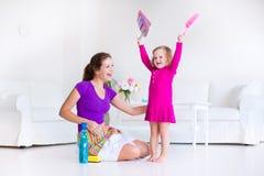 Moder och dotter som sopar golvet Arkivbild