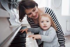 Moder och dotter som spelar det vita pianot, slut upp wiew royaltyfri fotografi