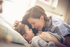 Moder och dotter som spelar i säng fotografering för bildbyråer
