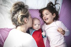 Moder och dotter som spelar med hans nyfödda familjemedlem Royaltyfria Bilder
