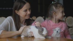 Moder och dotter som spelar med kanin lager videofilmer