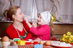 Moder och dotter som spelar med mjöl royaltyfria foton