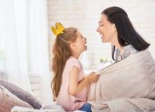 Moder och dotter som spelar och kramar Arkivbild