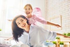 Moder och dotter som spelar och kramar Arkivfoto