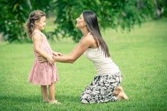 Moder och dotter som spelar på gräset på dagtiden Arkivfoton