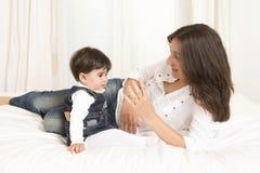 Moder och dotter som spelar på isolerad säng Royaltyfri Fotografi