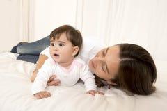 Moder och dotter som spelar på isolerad säng Arkivbild