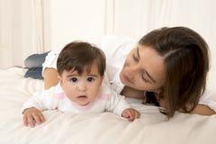 Moder och dotter som spelar på isolerad säng Royaltyfri Bild