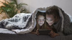 Moder och dotter som spelar på touchpad i säng stock video