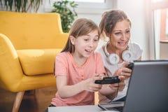 Moder och dotter som spelar videospel royaltyfria foton