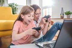 Moder och dotter som spelar videospel arkivfoto