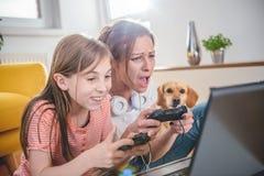 Moder och dotter som spelar videospel arkivfoton
