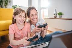 Moder och dotter som spelar videospel royaltyfri bild